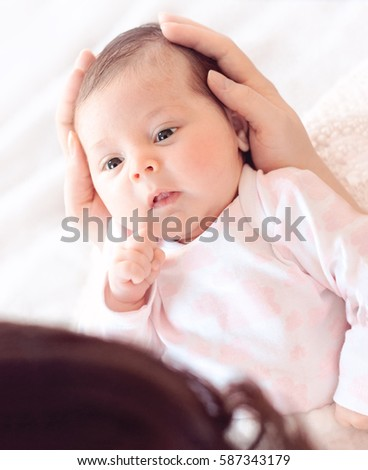 Gently mother hands holding baby . Plump and beautiful newborn stares at her mother. gentle.