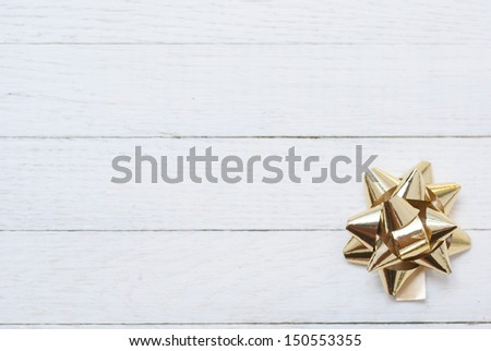 gift bow on white wooden table - stock photo