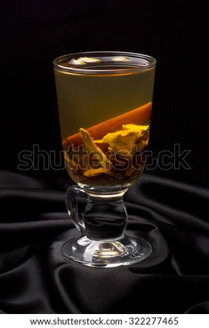Ginger tea with orange and ginger on the black atlas background - stock photo
