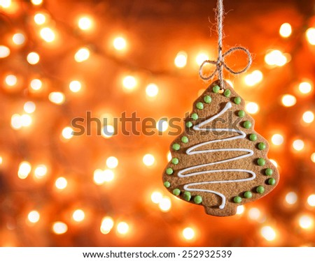 Gingerbread cookie hanging over bokeh lights background in a christmas theme  - stock photo