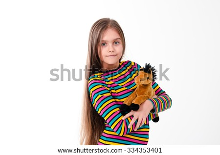 girl and a horse toy. beautiful girl with long hair plays a toy horse - stock photo