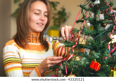 girl decorate the Christmas tree in a house interior - stock photo