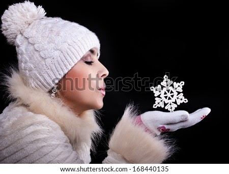 Girl in a fur coat, hat, and gloves on a black background blows away with the palms snowflake - stock photo