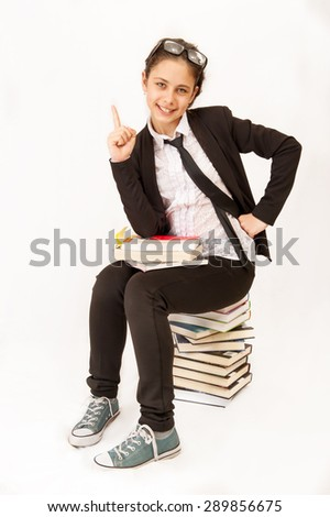 girl in a school uniform sits on textbooks, pointing her finger up - stock photo