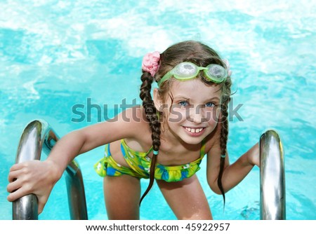 Girl in protective goggles leaves pool. Summer.