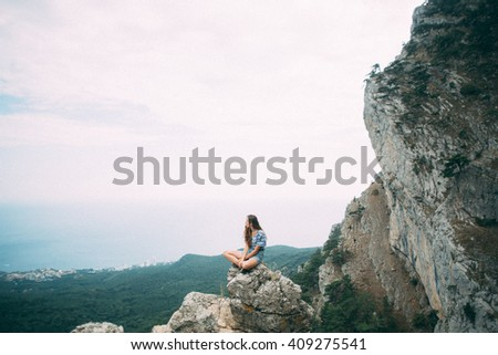 Girl in shorts and with long hair is sitting on a large stone at the end of the cliff . In terms  forests and mountains