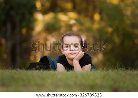 girl laying on a grass and daydreaming on a nice day in fall - stock photo