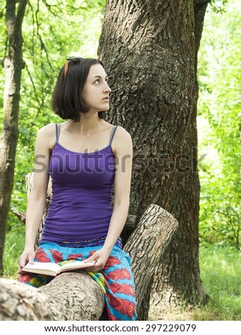 Girl lying on green grass and looking at the book.