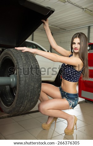 girl mechanic replace tires on wheels - stock photo