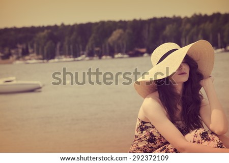 girl on beach , she is wearing floral dress hat , she enjoy the sun in the beautiful day.lake and boats in background.vintage color  - stock photo