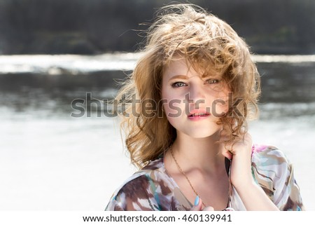 girl on the bank of the river with developing the wind hair