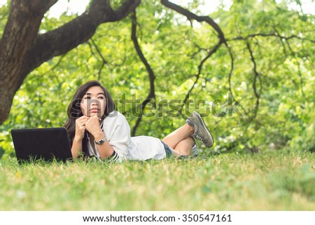 girl on the lawn outside the computer - stock photo