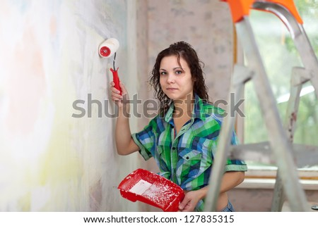 girl paints wall with roller at home - stock photo