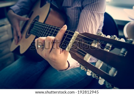 Girl plays a guitar, Toned - stock photo