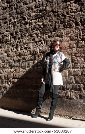 Girl posing at the stone wall - stock photo