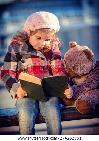 girl reads the interesting children's book to a toy bear - stock photo