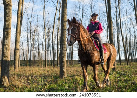 Girl riding a horse on autumn forest - stock photo