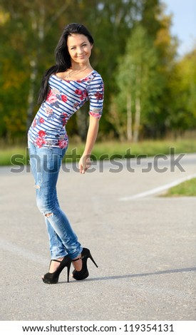 girl shows her slender figure walking in nature - stock photo