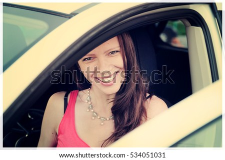 Girl sitting behind the wheel of his white car and smiles, holding the handlebars, Novosibirsk, Russia