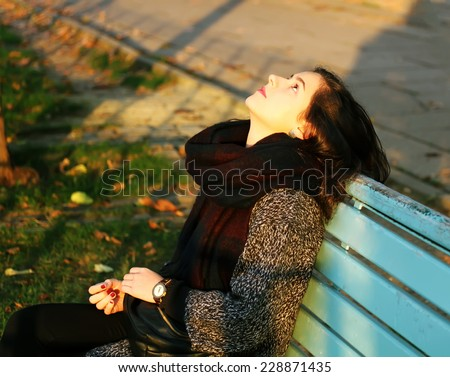 Girl sitting on the bench in the autumn in park - stock photo