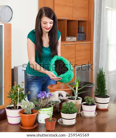 girl transplanting potted flowers at table - stock photo