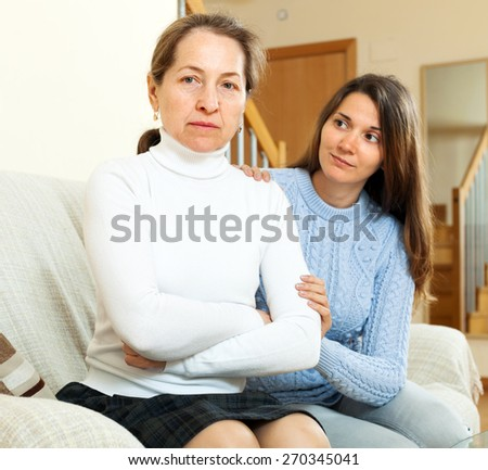 girl tries reconcile with  mature mother in home - stock photo