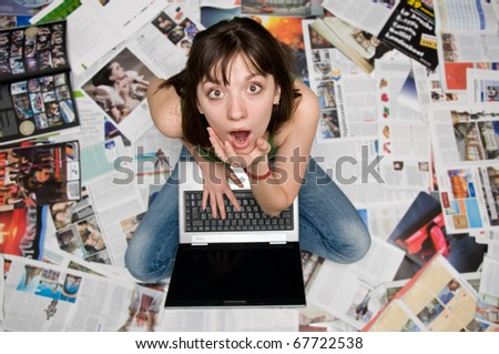 girl with a laptop sitting on newspapers - stock photo