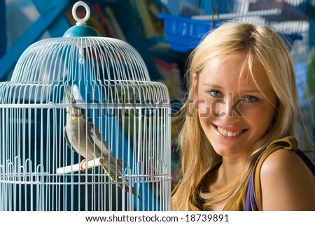 Girl with Parrot in a cage - stock photo