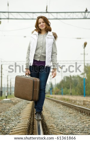 girl with suitcase walking along  railroad rail - stock photo
