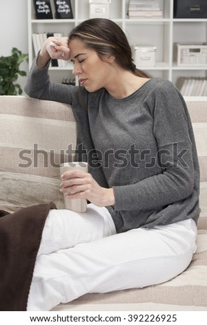 Girl with the flu sit in a room and drinking tea - stock photo