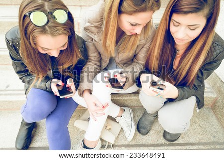 Girls typing on mobile phones - Three friends holding smart phones and chatting - Students sitting outdoors on stairs and talking - stock photo