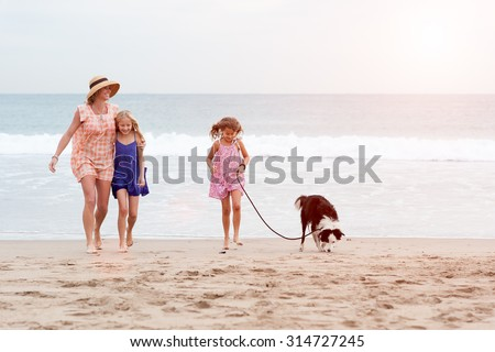 2 girls walking on beach with mom and dog. Happy family walking. - stock photo
