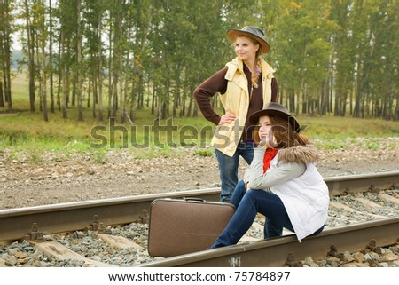 girls with suitcase walking along  railroad rail - stock photo