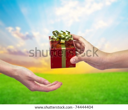 """""""Give and take"""" Gift box on hand to hand - stock photo"""