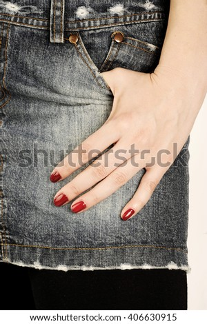 Glamorous girl wears jeans skirt and hand with fashion red nail polish  - stock photo