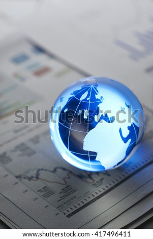 Glass globe on  stock market chart . shot with very shallow depth of field.