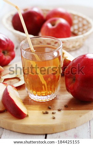 glass of apple juice with apples in the background