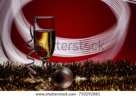 glass of champagne and Christmas ball on  festive Christmas  red background. new Year party