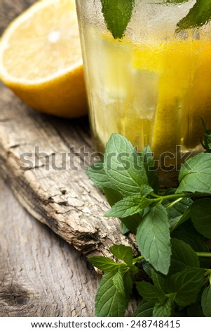 glass of lemonade, mint and lemon on wooden background - stock photo
