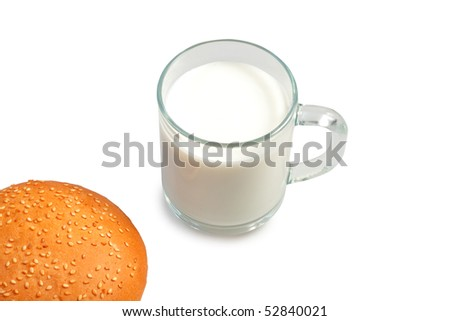 glass of milk and bun on table