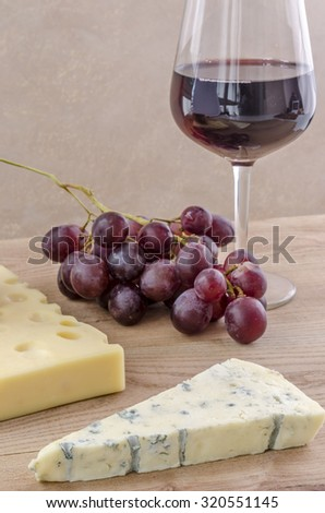 Glass of red wine with cheeses and grape over wood.