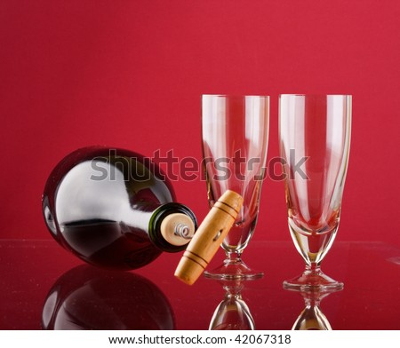 Glass of red wine with glass and bottle - stock photo