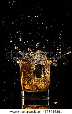 Glass of whiskey with splash, isolated on black background - stock photo