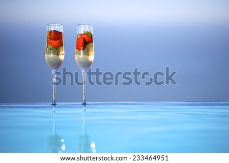 2 Glasses of Champagne with strawberries on the edge of an infinity pool. - stock photo