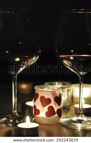 2 glasses of wine lit by only candle light, with a romantic theme - stock photo
