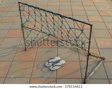 Goal post sport outdoor soccer football with  slippers on footpath Mekong River Thailand