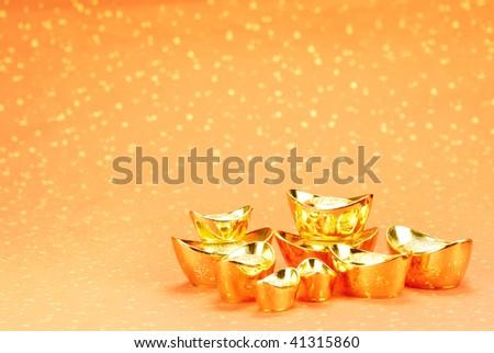 Gold ingot on a festive background. - stock photo
