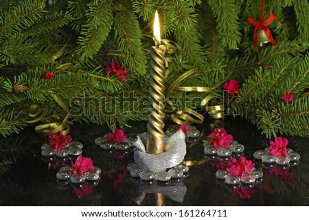 golden burn candle under  Christmas tree  - stock photo