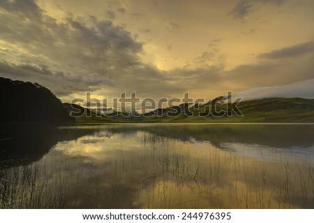 GOLDEN SUNSET. After the sun has dropped behind the escarpment, high cloud reflects the light in the waters of a lake, Giant's cup Wilderness Reserve, Kwazulu Natal, South Africa - stock photo