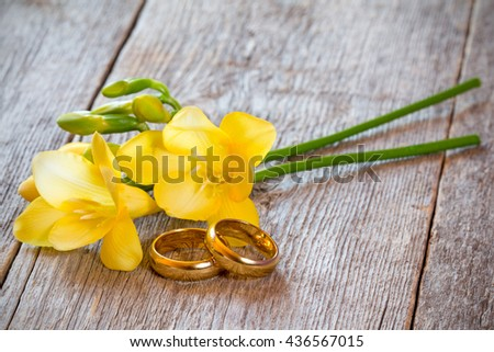 Golden wedding rings with freesia flower on wooden background - stock photo